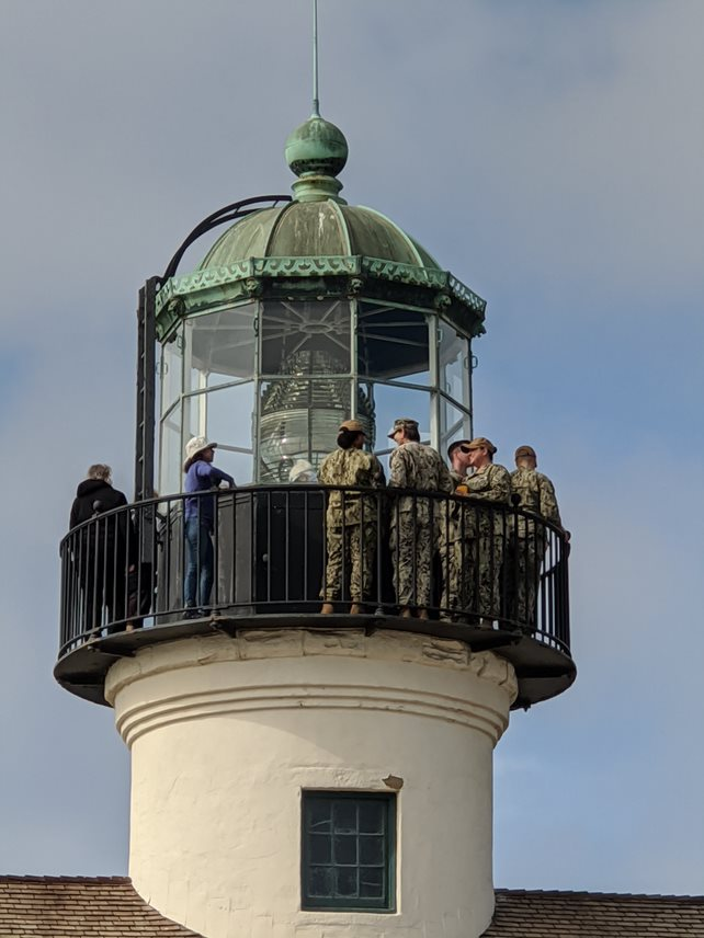 A view of the lighthouse tower. Five service members enjoy the view from the black iron lens deck, while volunteer Mayra stands by for questions. The Fresnel lens is visible in the center of the catwalk.