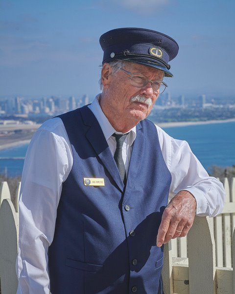 Volunteer Jack, wearing the dark blue vest and hat of a 19th century lighthouse keeper leans against the white picket fence of the rain catchment basin. The bay and San Diego are visible in the distance.