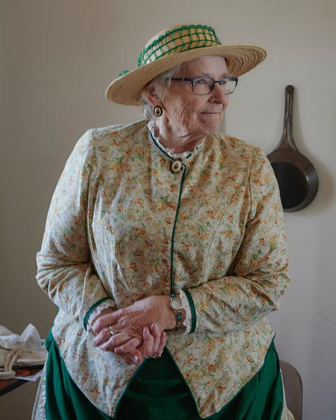 Volunteer Suzanne wearing a light yellow floral top and dark green dress in the style of the 19th century. Eileen is standing in the kitchen of the lighthouse with a large cast iron pan hanging from the wall behind her.