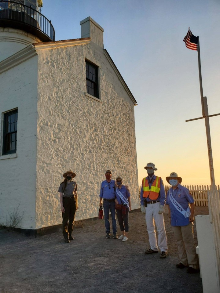 Park Ranger Julieanne, park volunteers Dan and Becky Wieder, Jose, and Sandy stand near the white brick wall of the lighthouse with the American flag behind them. All are wearing face masks. Becky and Sandy are wearing sashes across their uniforms that say Votes for Women.