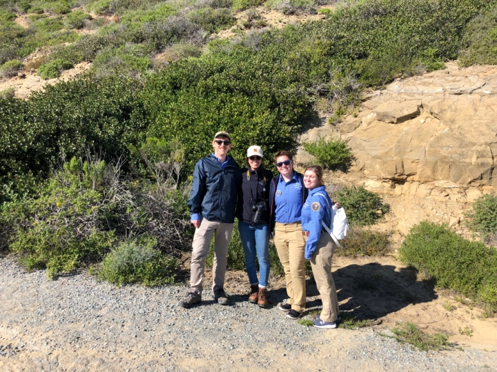From left to right, park apprentice Wyler, CVA Setareh, park apprentice Ryan, and park apprentice Brooke smile and stand facing the camera. Behind them are patches of green plants running up a cliff.