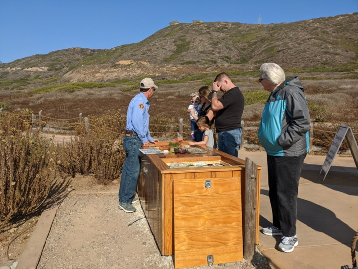 Park volunteer Dan stands behind the tidepool Education Table talking to two children and three adults about what they can find in the tidepools. The cement portion of the Coastal Trail is in the background along with brown and green bushes.