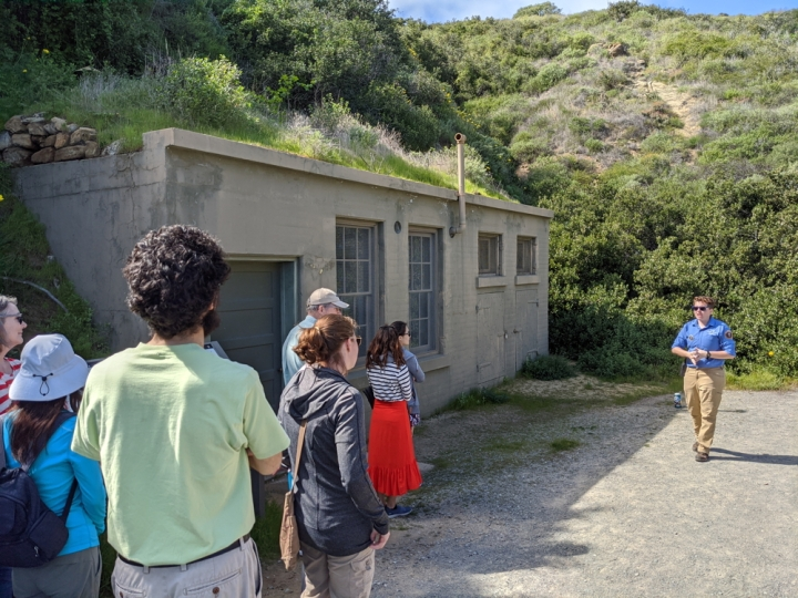 Apprentice Ryan leads a hike down the bayside trail for a group of visitors and volunteers. Ryan is stopped at the olive green generator station, which is built into the slope of the hill.