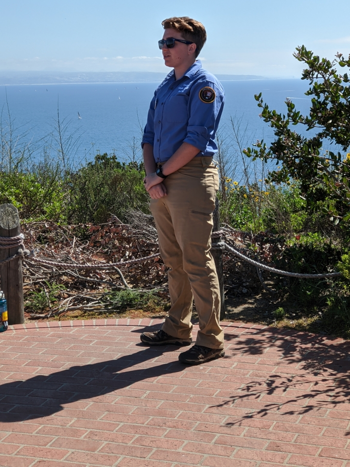 Apprentice Ryan leads a hike near the visitor center. Ryan is standing with hands clasped together and relaxed at waist level, atop a red brick overlook that has views towards the bay.