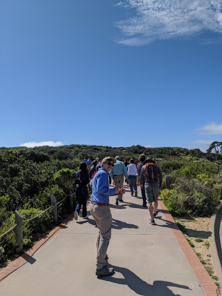 A view from behind as a large group of volunteers and staff head up the path that leads to the lighthouse. Apprentice Wyler, who is bringing up the rear of the group, turns to face us with a smile and a thumbs up.