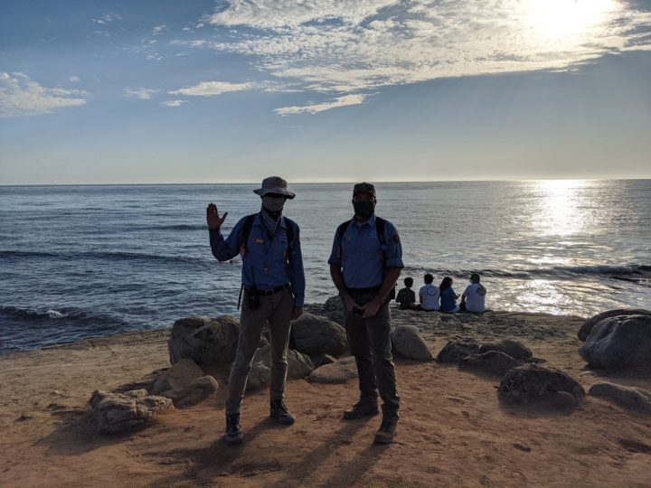 VIPs Jose & Brian stand and pose on a sandy cliff in front of sunset over the water. 4 visitors sit on the edge of the cliff behind them and look out at the water.