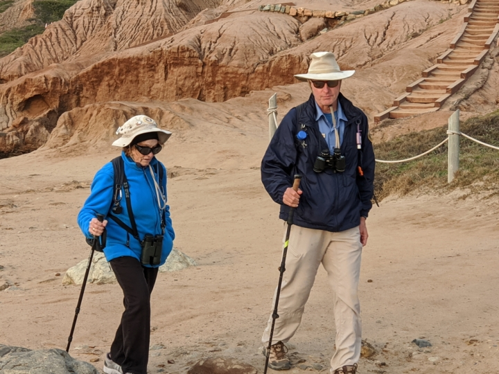 VIPs Elke & Bob walk along a dirt path near steps on a sandstone cliff. They wear a jacket, sunglasses, binoculars, and use a hiking stick.