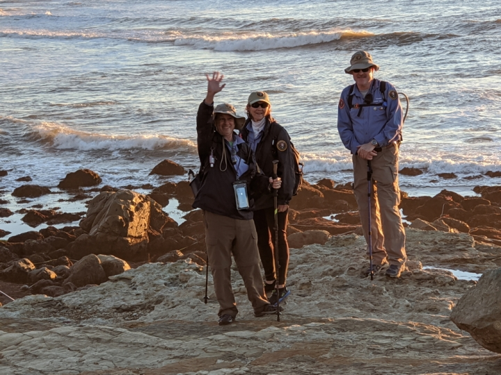 VIPs Dan, Mary, & Sean stand and pose on an uneven, dry path in front of small, brown boulders, and the vast ocean with white-topped waves.
