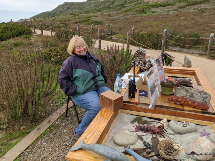 VIP Mona wears a big smile and a zipped-up jacket as she sits behind a table full of marine mammal models.