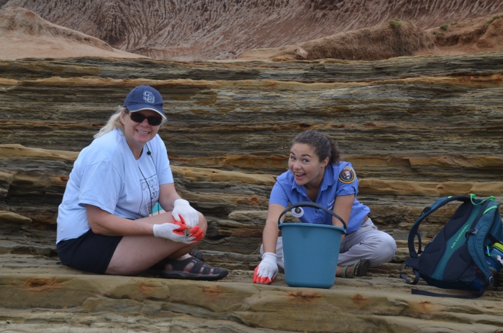 Two volunteers wearing red and orange gloves sit on a flat surface at the tidepools. In front of the volunteer on the right is a blue bucket and beside her is a green and blue backpack.