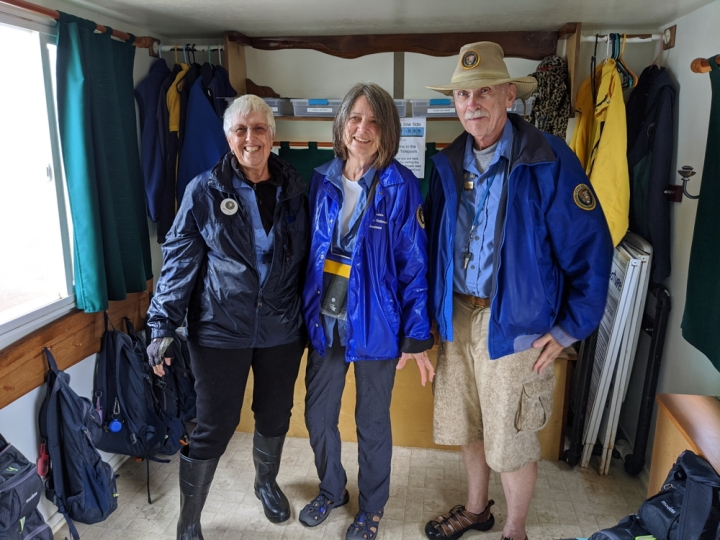 Tidepool VIPs Eileen, Gayle, and Patrick smiling and wearing blue windbreakers in the tidepool trailer. Eileen is wearing rubber boots while Gayle and Patrick wear closed-toed water sandals.