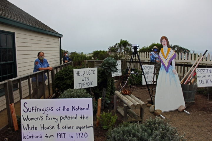 "Lighthouse garden with projector on tripod set up in the middle of garden path. In the garden are a wooden illustrated cutout of a women in a white dress with purple and yellow sash and white signs staked into the ground. Visible sign text reads, ""Suffragists of the National Women's Party picketed the White House & other important locations from 1917 to 1920"" and ""Help us to win the vote."" VIP Pam wears a face mask and stands along wooden fence outside the garden and two other VIPs stand further away also along fence and with masks."