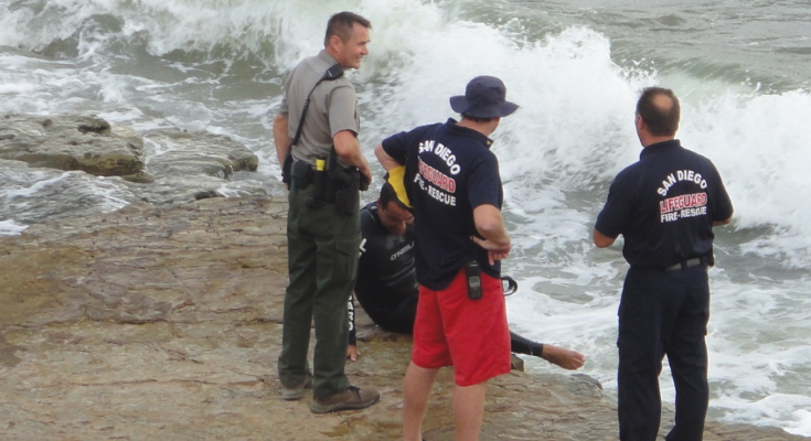 A park ranger stands with several lifeguards at a rocky shoreline. The lifeguards are attempting to rescue an injured visitor.