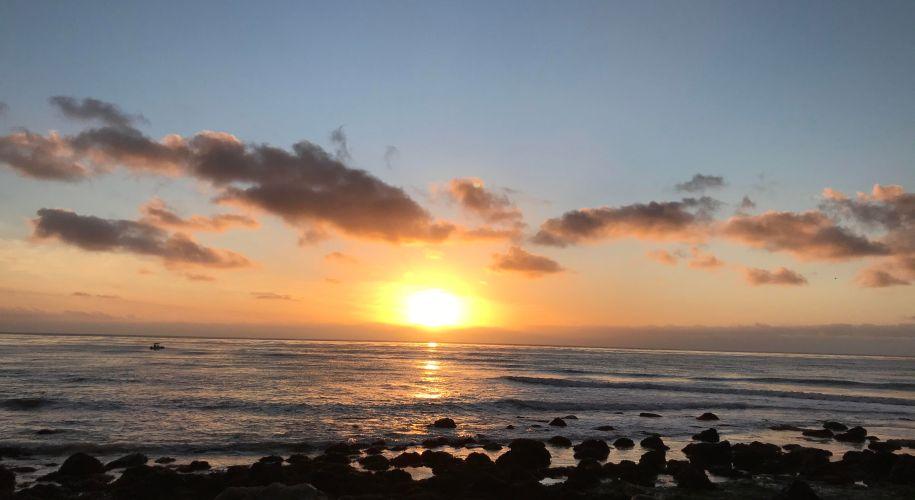 A sunset along a rocky shoreline.