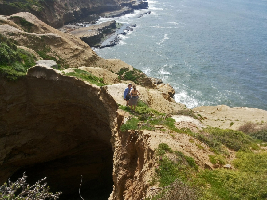Two people stand at a dangerous edge of a sinkhole along sandstone cliffs at the ocean's edge.