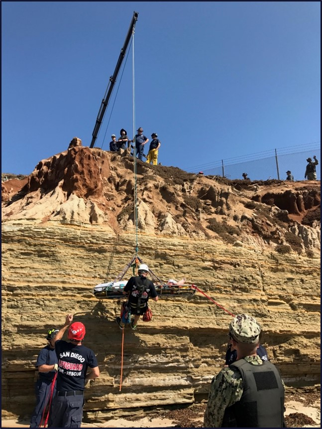 Lifeguards use a crane to raise an injured person along sandstone cliffs.