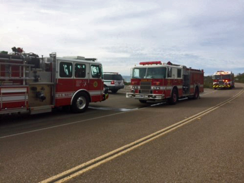 Two firetrucks are parked along a road.