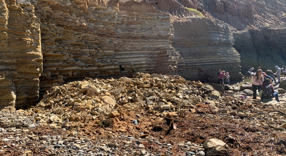 Broken sandstone rocks against a layered cliff. Several people are in the background looking at the rock fragments.