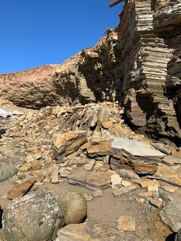 Broken sandstone rocks against a layered cliff.