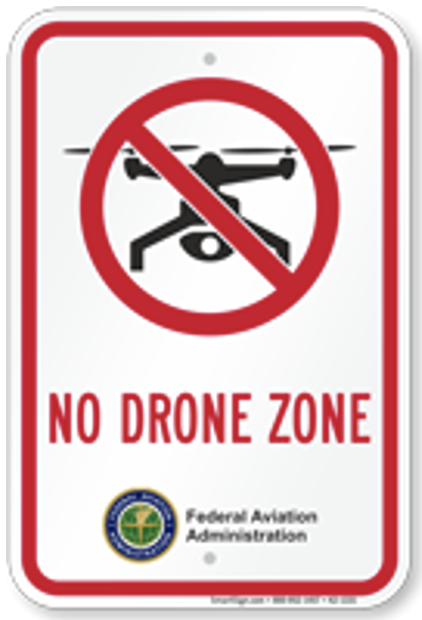 """White rectangular sign with red border. A drawing of a Drone is covered with a red circle and a slash. Below are the words """"No Drone Zone"""""""