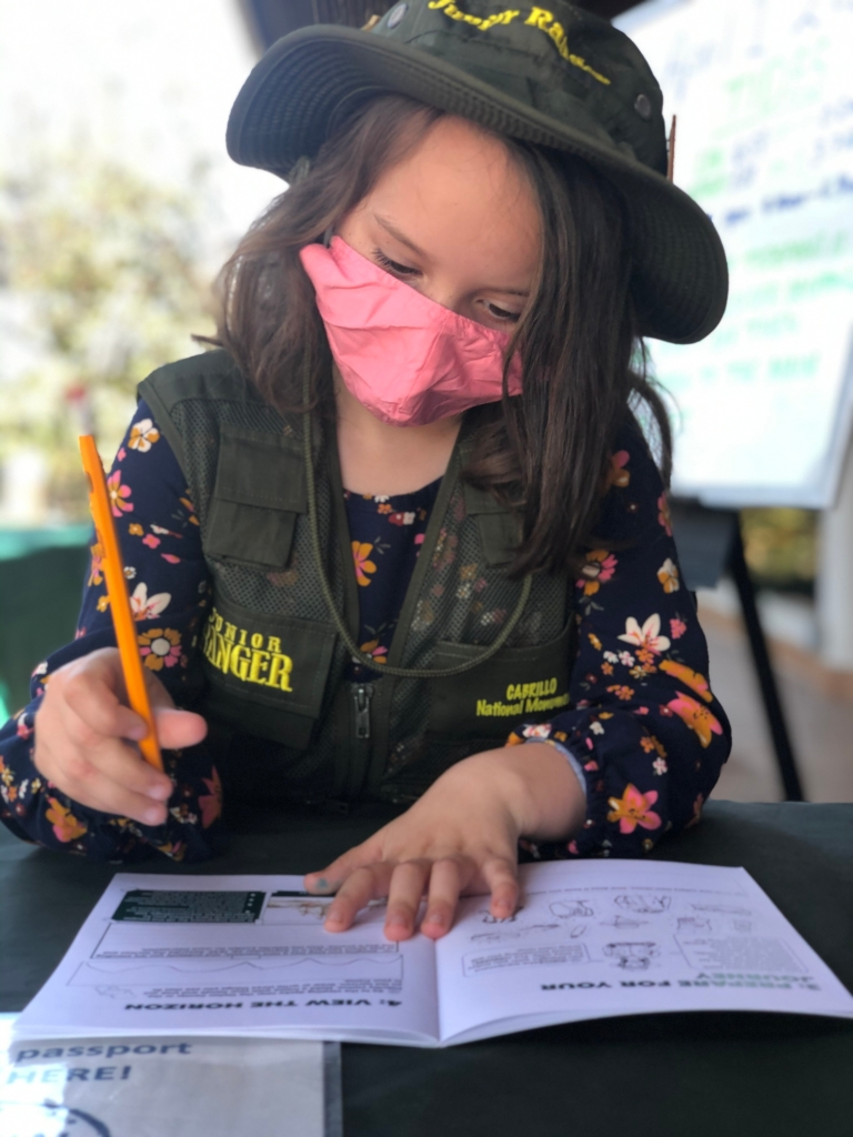 A girl with a pink face mask, junior ranger hat and vest, fills out her Junior Ranger booklet