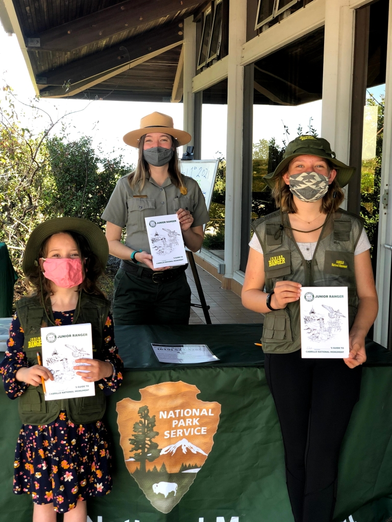 A Park ranger stands between two girls with their Junior Ranger booklets.