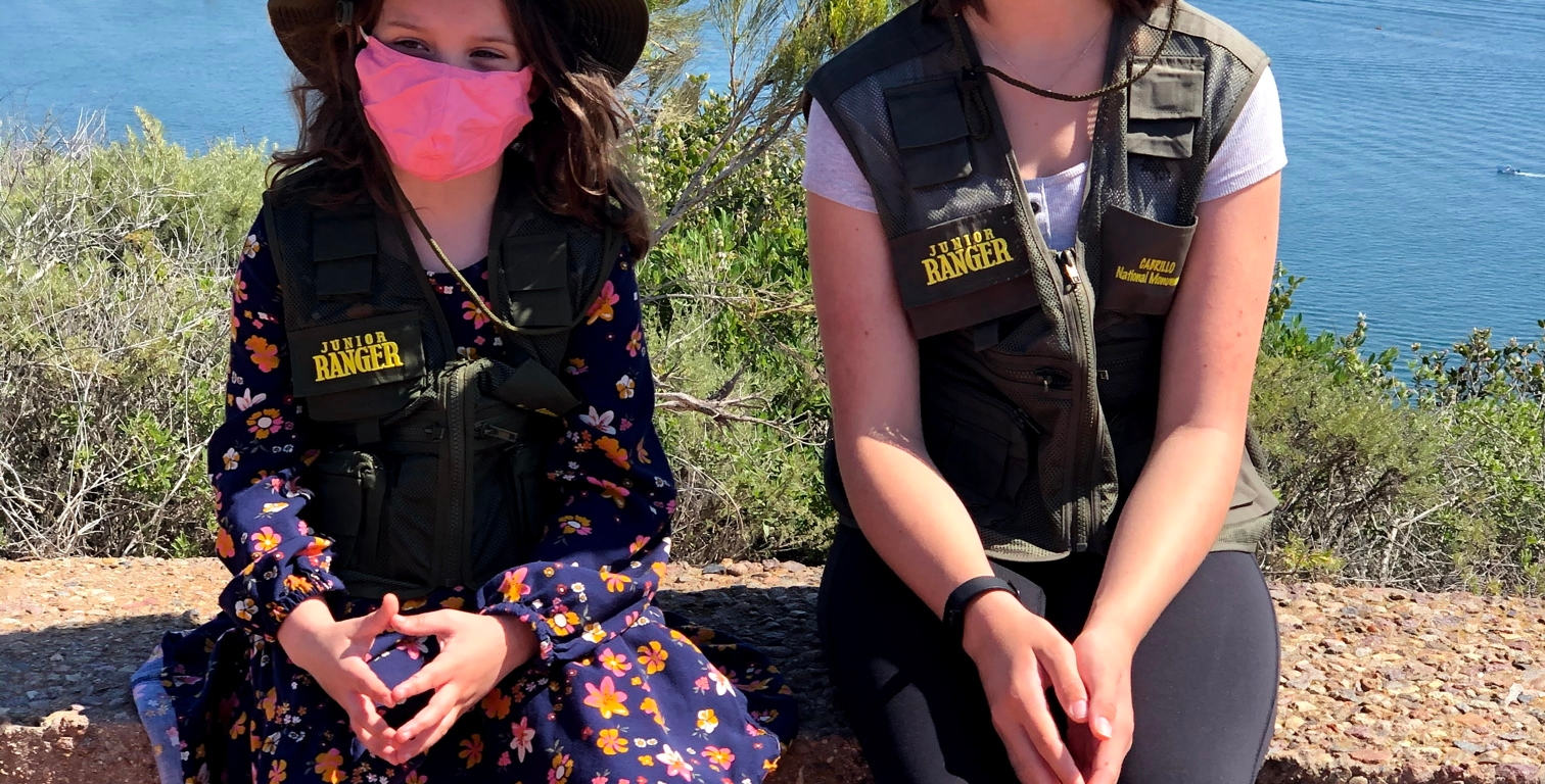 Two girls wear thei Junor Ranger hats and vests, sit on a stone wall with the blue water of San Diego Bay behind them.