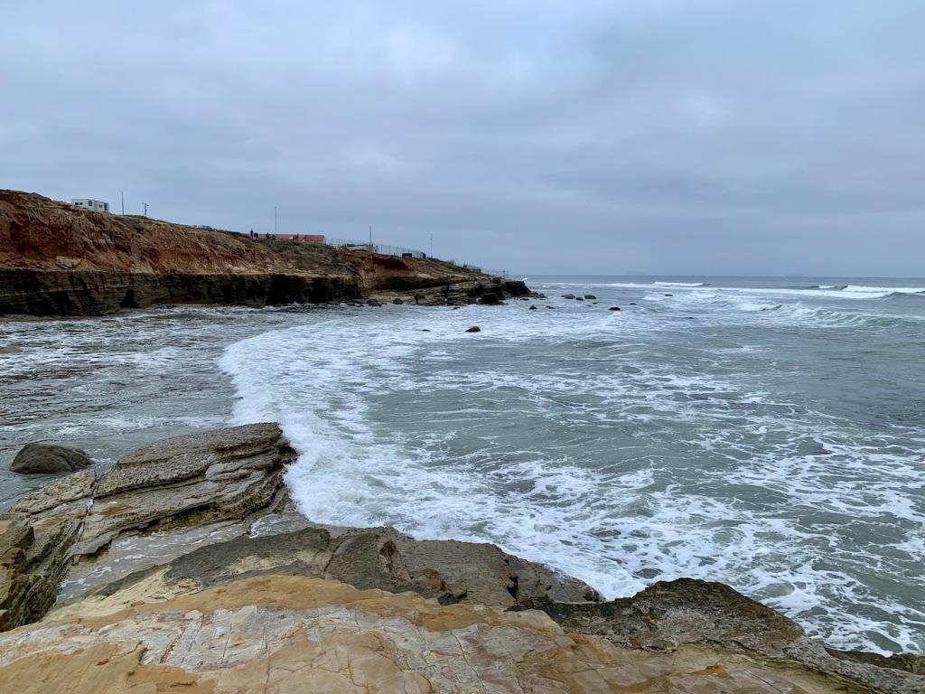 The ocean along a rocky cliff with a gray sky.