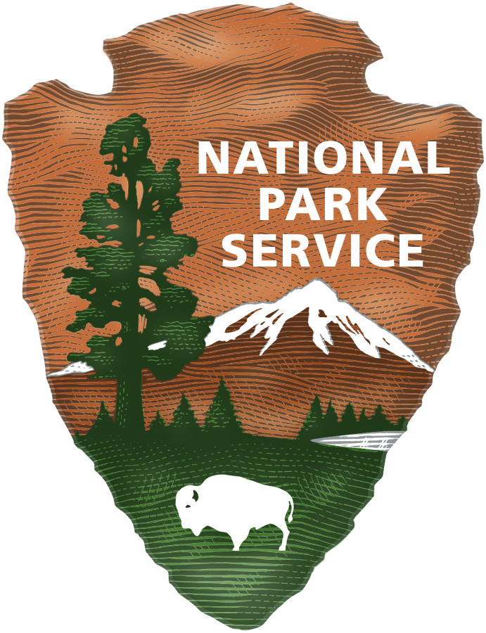 An arrowhead representing the National Park Service. A tall tree on the left, snow capped mountain on the right with buffalo at the bottom.
