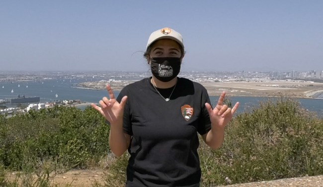 Woman in hat and shirt with National Park Service arrowhead logo holds up both hands with thumb, pointer finger, and pinky finger extended. Behind her a waterway with boats and city skyline are visible.