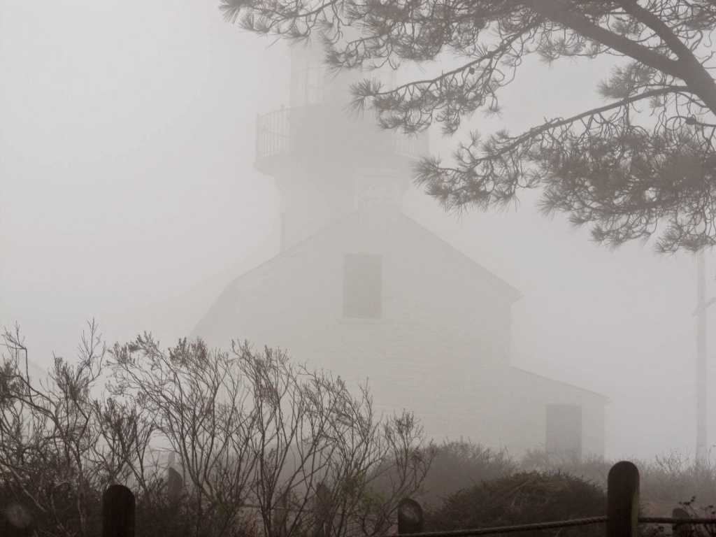 A lighthouse shrouded in a gray fog.
