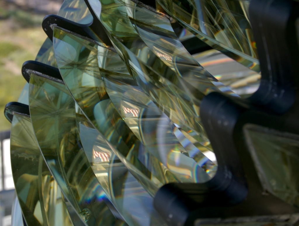 Pieces of glass from a lighthouse lens with an american flag reflecting on it.
