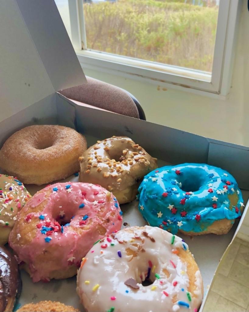 A box of different colored doughnuts.