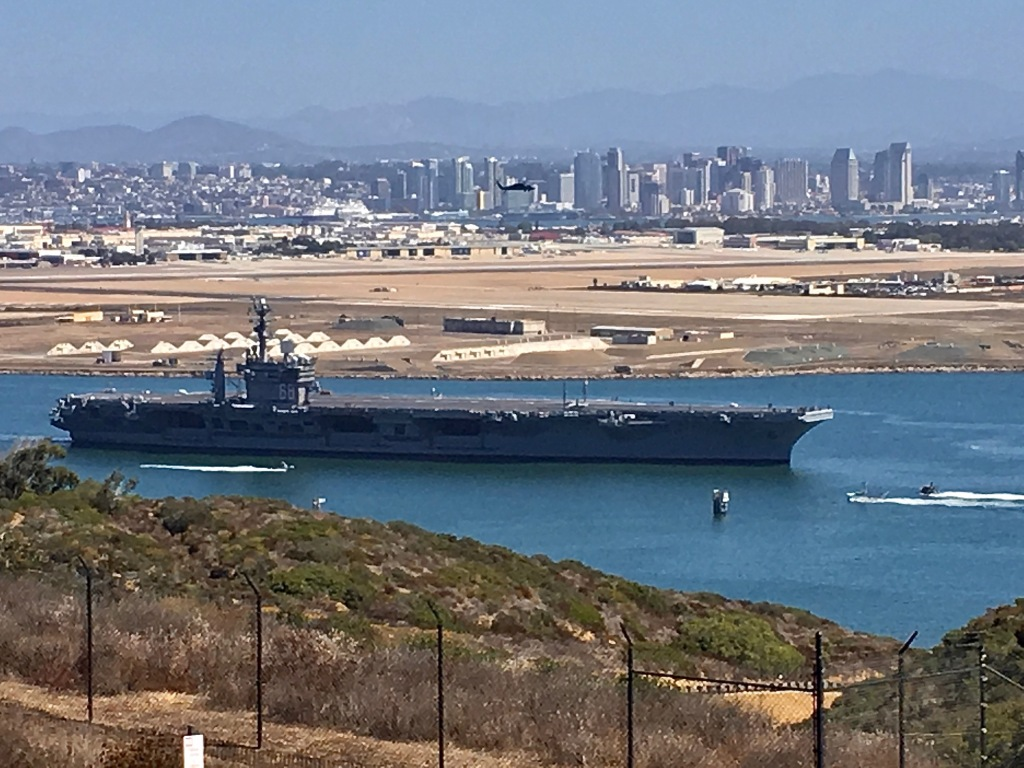 A large gray ship with a flat top in the water with the city skyline in the background.