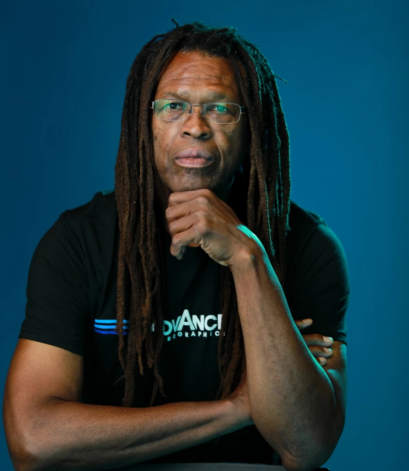 A man in a black shirt, long hair and glasses