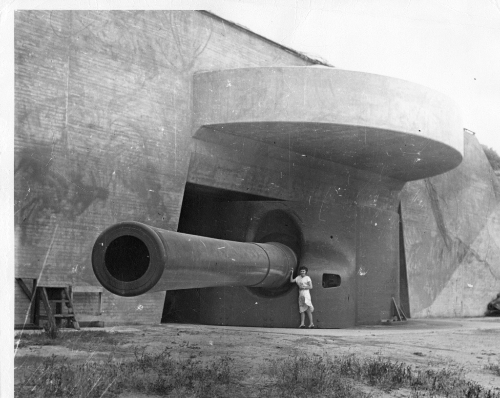 A woman stands next to a large cannon sticking out of a building.