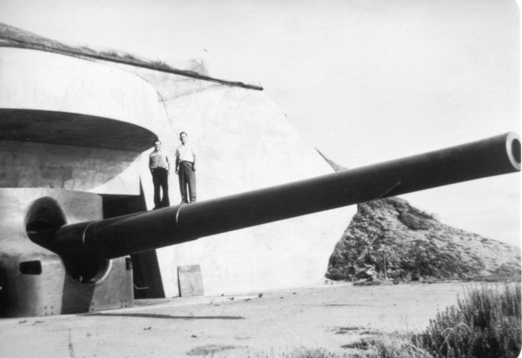 A large cannon sticks out of a building. Two people stand on top of the cannon.