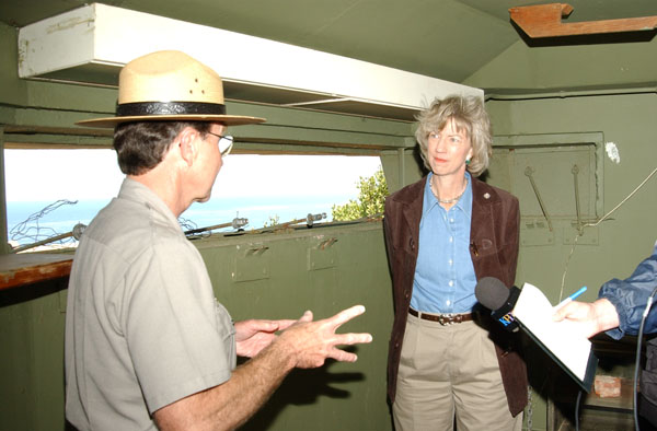 A man talks with a woman inside a bunker room. The window is open showing the ocean in the background.