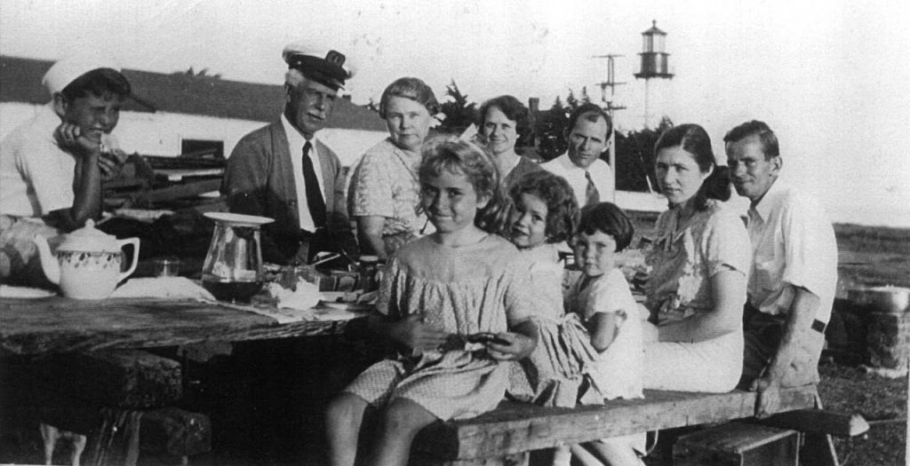 A family sits around a picnic table. A lighthouse is in the distance.