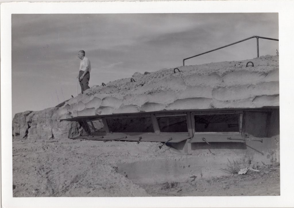 A bunker built into a hillside. A curved concrete roof blends into the background. A man stands on top of the roof.