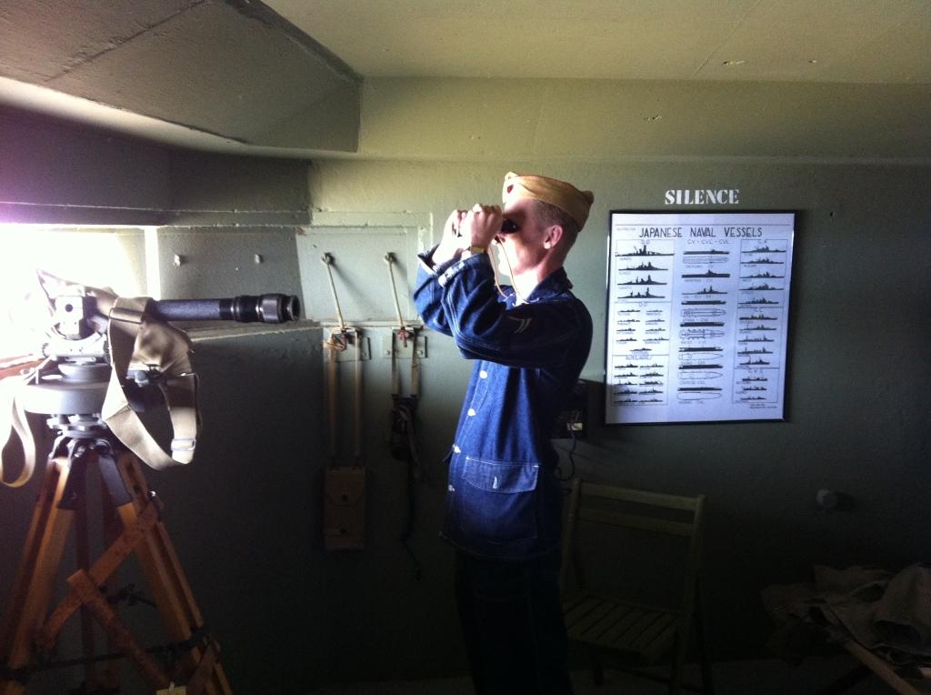 A man wearing World War II uniform looks through binoculars out a window in a bunker.