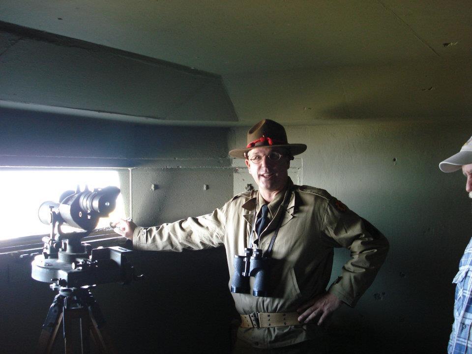 A man in World War II uniform stands next to telescope.