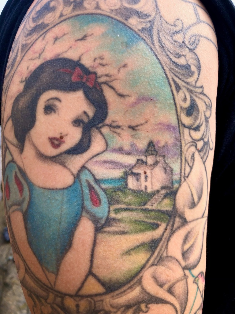 A tattoo on an arm showing a woman and a house inside an oval.